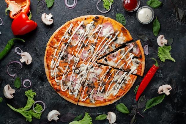 Pizza z szynką i pieczarkami na ciemnym tle z warzywami, papryką, mozzarellą i bazylią. widok z góry na ciemny kamienny stół