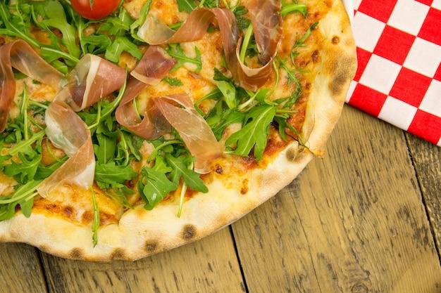Pizza z szynką i rukolą na drewnianym stole, widok z góry