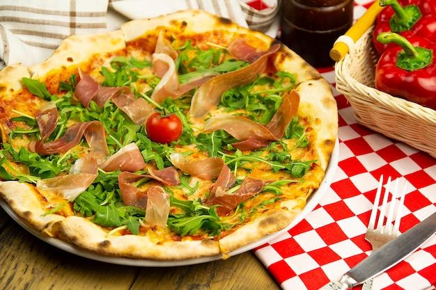 Pizza z szynką i rukolą na drewnianym stole