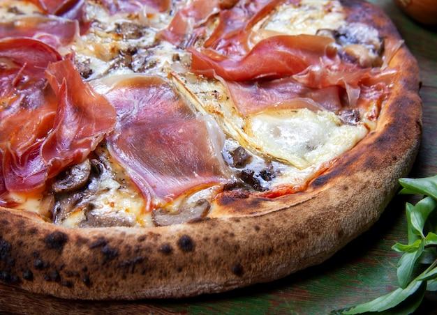 Pizza z szynką parmeńską pieczona w piecu opalanym drewnem