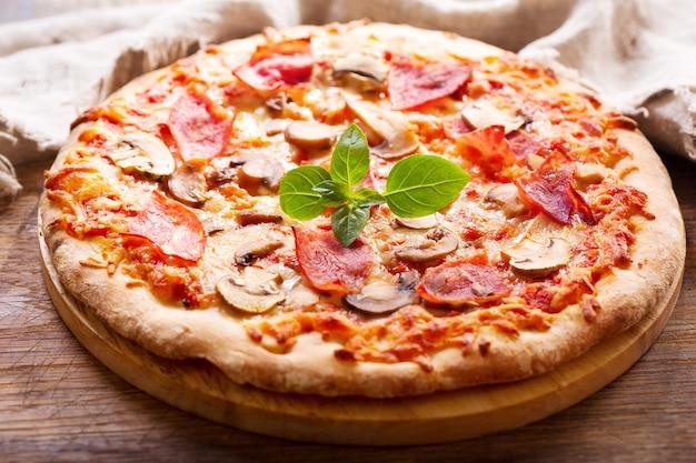 Pizza z szynką, salami i pieczarkami na drewnianym stole