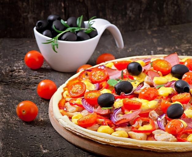 Pizza z warzywami, kurczakiem, baleronem i oliwkami odizolowywającymi na bielu