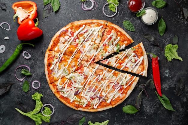Pizza z warzywami, papryką, mozzarellą i bazylią. widok z góry na ciemny kamienny stół