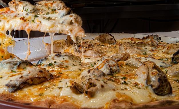 Pizza ze specjalnym smakiem mozzarelli z ostrygami i drobnymi ziołami podana na białym talerzu