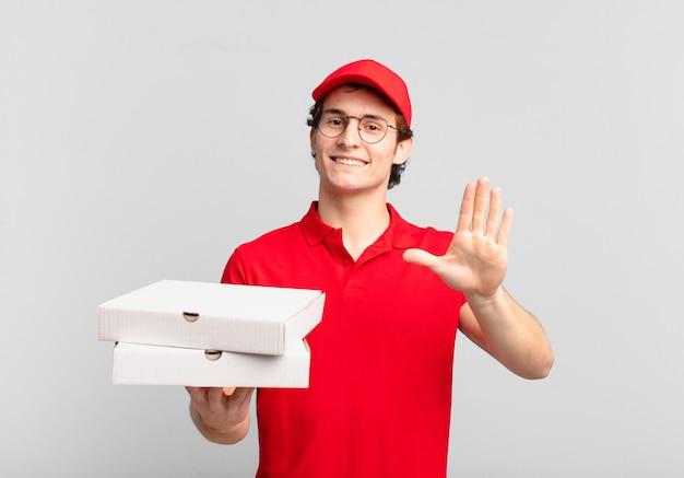 Pizzę dostarcza chłopiec uśmiechnięty radośnie i radośnie, machający ręką, witający i pozdrawiający lub żegnający się