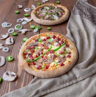 Pizze z siekaną kiełbasą, mięsem, cebulą, pieczarkami i zielonym pieprzem