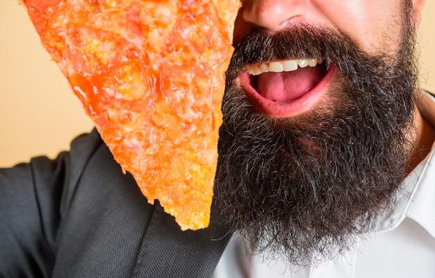 Pizzeria brodaty mężczyzna trzyma kawałek pizzy fastfood brodaty mężczyzna je pizzę mężczyzna je świeży kawałek pizzy
