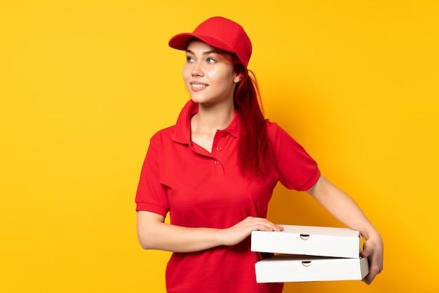 Pizzy doręczeniowa dziewczyna trzyma pizzę nad odosobnioną ścianą patrzeje strona