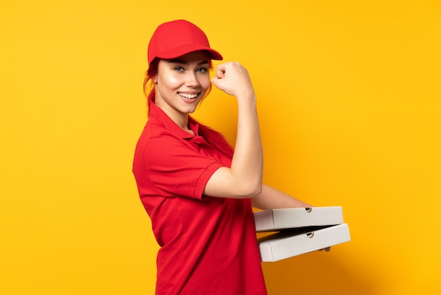 Pizzy doręczeniowa dziewczyna trzyma pizzę nad odosobnioną ścianą świętuje zwycięstwo