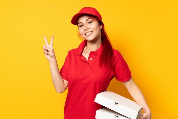 Pizzy doręczeniowa dziewczyna trzyma pizzę nad odosobnioną ścianą uśmiecha się zwycięstwo znaka i pokazuje