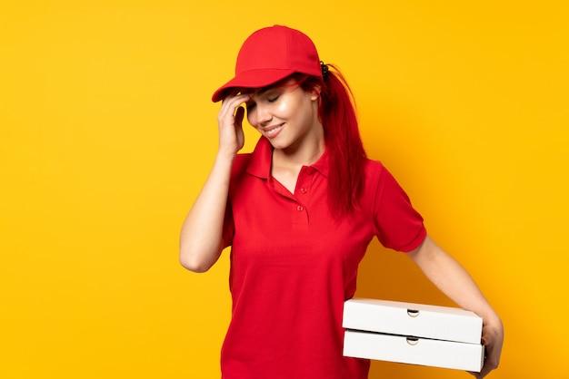 Pizzy doręczeniowa dziewczyna trzyma pizzę nad odosobniony ścienny śmiać się
