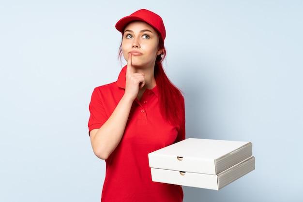 Pizzy doręczeniowa dziewczyna trzyma pizzę nad odosobnionym mieć wątpliwości podczas gdy przyglądający up
