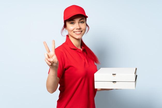 Pizzy doręczeniowa dziewczyna trzyma pizzę nad odosobnionym ono uśmiecha się i pokazuje zwycięstwo znakiem