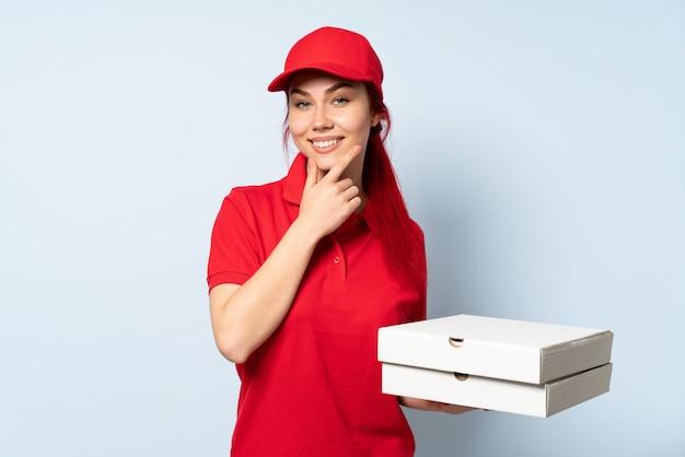 Pizzy doręczeniowa dziewczyna trzyma pizzę nad odosobnionym szczęśliwym i uśmiechniętym