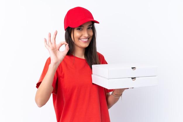Pizzy doręczeniowa kobieta trzyma pizzę nad odosobnioną biel ścianą pokazuje ok znaka z palcami