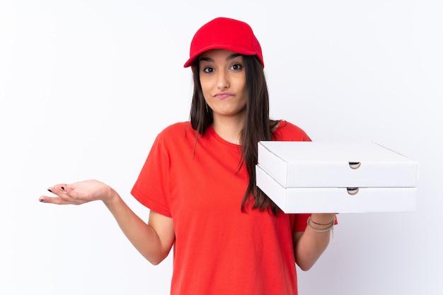 Pizzy doręczeniowa kobieta trzyma pizzę nad odosobnioną biel ścianą robi wątpliwość gestowi podczas gdy podnoszący ramiona