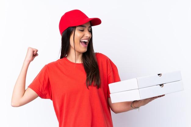 Pizzy doręczeniowa kobieta trzyma pizzę nad odosobnioną biel ścianą świętuje zwycięstwo