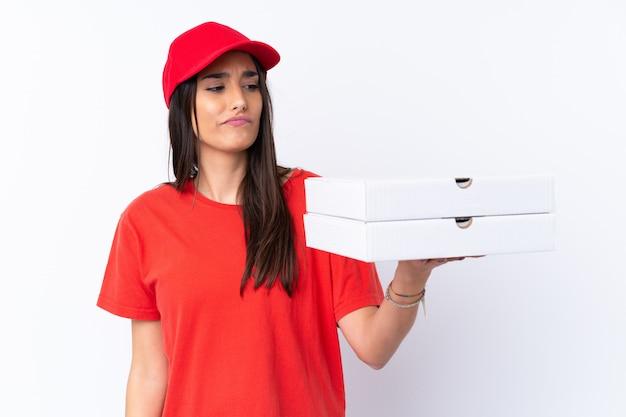 Pizzy doręczeniowa kobieta trzyma pizzę nad odosobnioną biel ścianą z smutnym wyrażeniem
