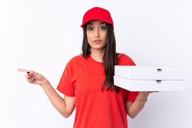 Pizzy doręczeniowa kobieta trzyma pizzę nad odosobnioną biel ścianą zaskakującą i wskazuje stronę