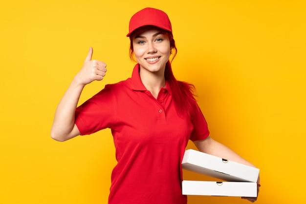 Pizzy doręczeniowa kobieta trzyma pizzę nad odosobnioną ścianą daje aprobata gestowi