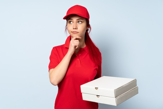 Pizzy doręczeniowa kobieta trzyma pizzę nad odosobnioną ścianą ma wątpliwości i główkowanie