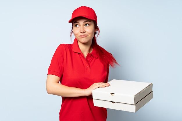 Pizzy doręczeniowa kobieta trzyma pizzę nad odosobnioną ścianą robi wątpliwość gestowi podczas gdy podnoszący ramiona