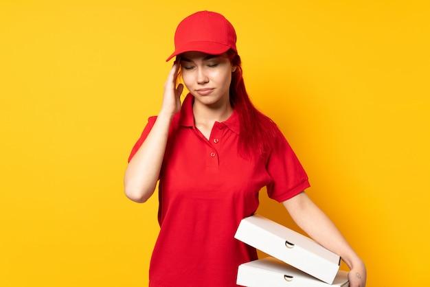 Pizzy doręczeniowa kobieta trzyma pizzę nad odosobnioną ścianą z migreną