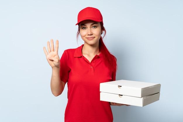 Pizzy dostawy dziewczyna trzyma pizzę nad odosobnioną ścianą szczęśliwą i liczy cztery z palcami