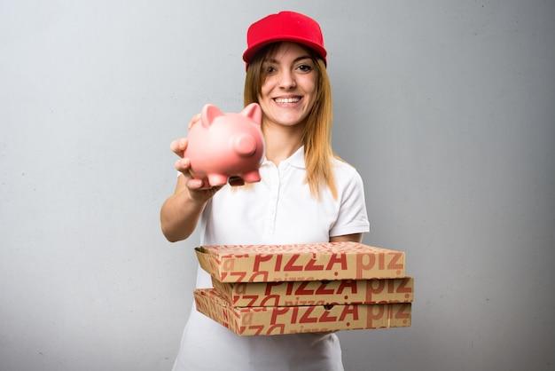 Pizzy dostawy kobieta trzyma piggybank na textured tle