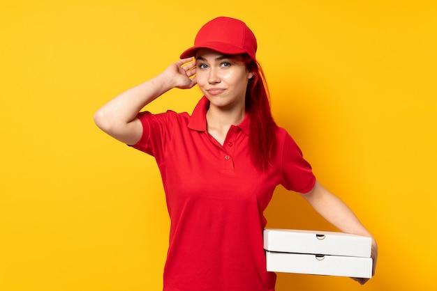 Pizzy dostawy kobieta trzyma pizzę nad odosobnioną ścianą ma wątpliwości