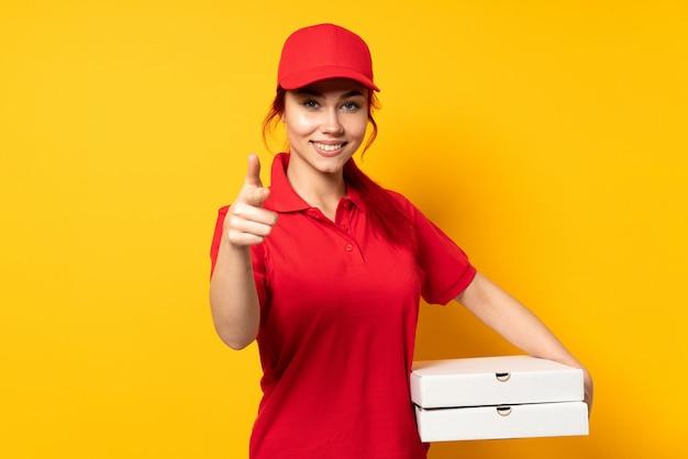 Pizzy dostawy kobieta trzyma pizzę nad odosobnioną ścianą wskazuje przód i ono uśmiecha się