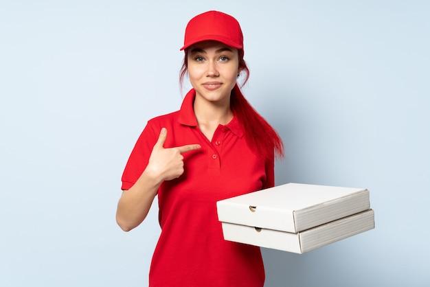 Pizzy dostawy kobieta trzyma pizzę nad odosobnioną ścianą z niespodzianka wyrazem twarzy