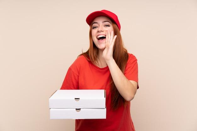Pizzy nastolatka doręczeniowa dziewczyna trzyma pizzę nad odosobnioną ścianą krzyczy z usta szeroko otwarty