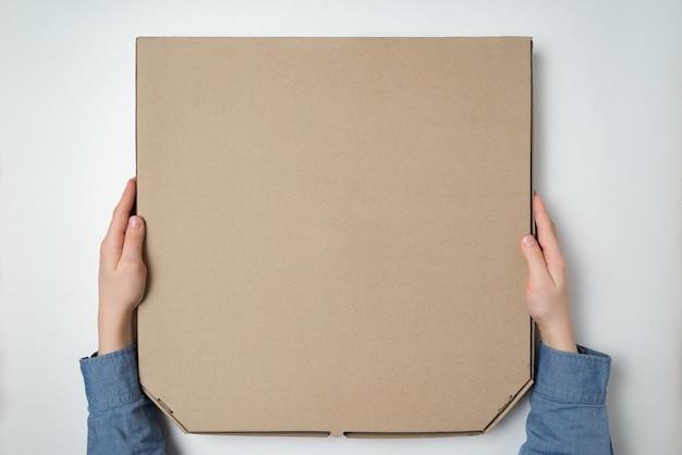 Pizzy pudełko w children rękach na bielu