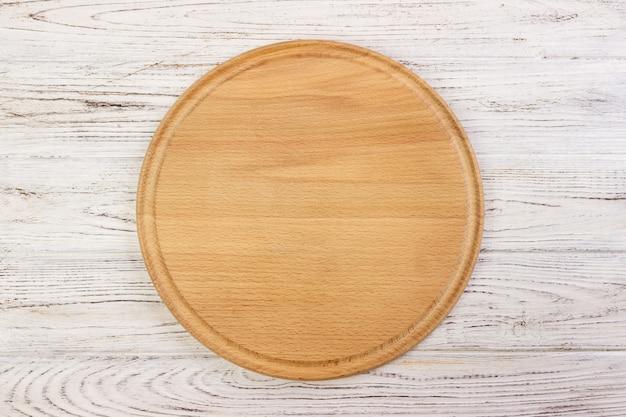 Pizzy tnąca deska przy stołowym tłem, round deska