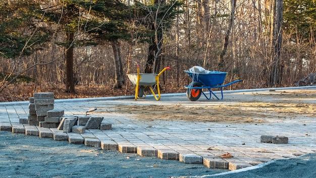 Plac budowy i kostka brukowa na ścieżce spacerowej w parku publicznym. miejsce prac przygotowawczych z wózkami do transportu ziemi. płytki chodnikowe w trakcie układania