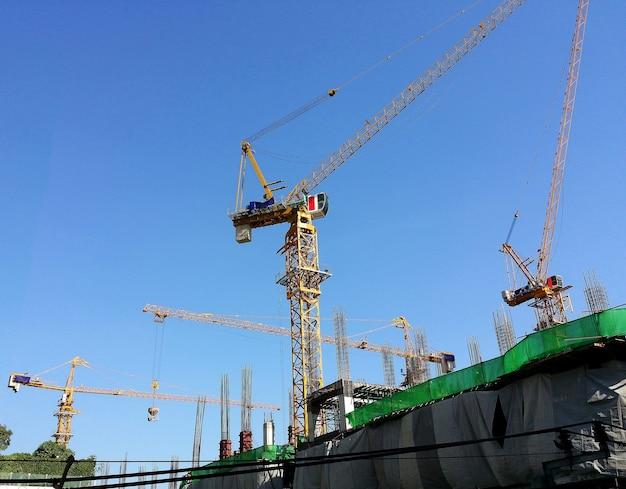 Plac budowy i żółty dźwig i budynek i błękitne niebo.
