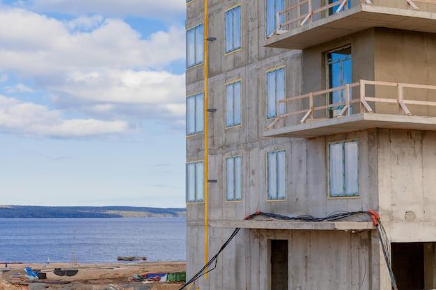 Plac budowy nad jeziorem i nowy dom z betonu i metalu. budowa wieżowca.