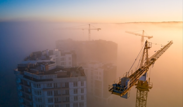 Plac budowy o świcie. żurawie wieżowe nad mgłą na tle porannego słońca. widok drona