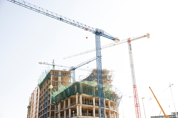 Plac budowy obejmujący kilka żurawi pracujących na kompleksie budynków