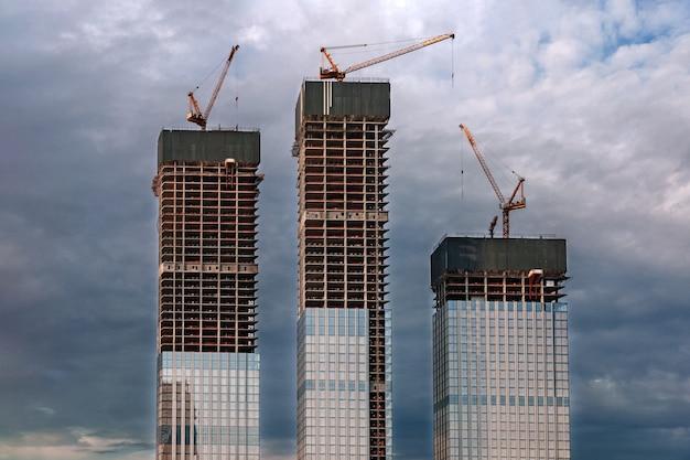 Plac budowy, wieżowce i dźwigi na zachmurzonym niebie