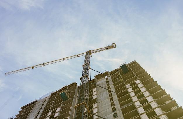 Plac budowy wraz z budynkami w trakcie budowy oraz wielopiętrowymi domami mieszkalnymi. żurawie wieżowe w akcji na tle błękitnego nieba