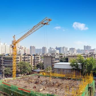 Plac budowy, wysokie wieżowce i dźwigi.