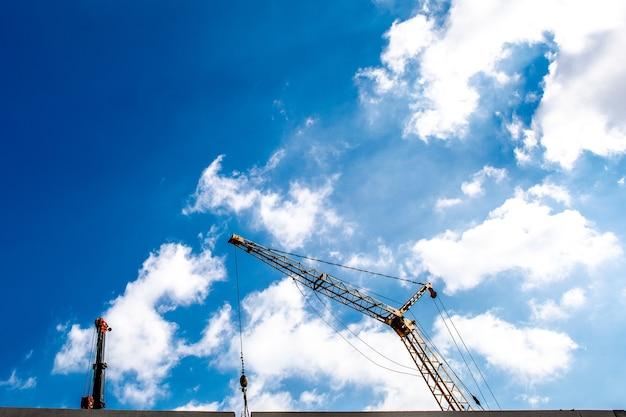Plac budowy z dźwigami na niebieskim niebie