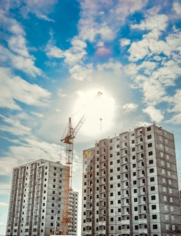 Plac budowy z dźwigami na tle nieba.