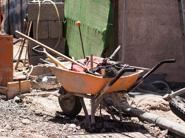 Plac budowy z taczką wypełnioną narzędziami