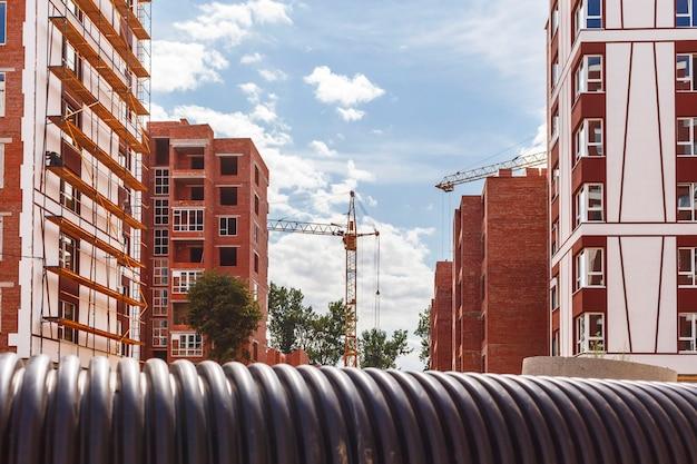 Plac budowy z wieżowcami z plastikową rurą na pierwszym planie z bliska