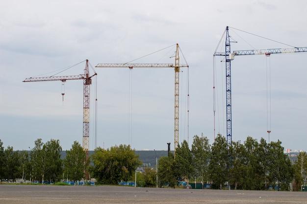 Plac budowy z wysokimi dźwigami na tle błękitnego nieba. w budowie jest budynek mieszkalny.