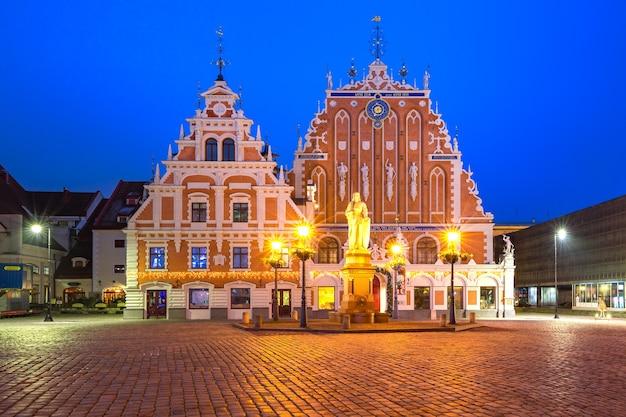 Plac ratuszowy z domem czarnogłowych i pomnikiem saint roland na starym mieście w rydze w nocy, łotwa