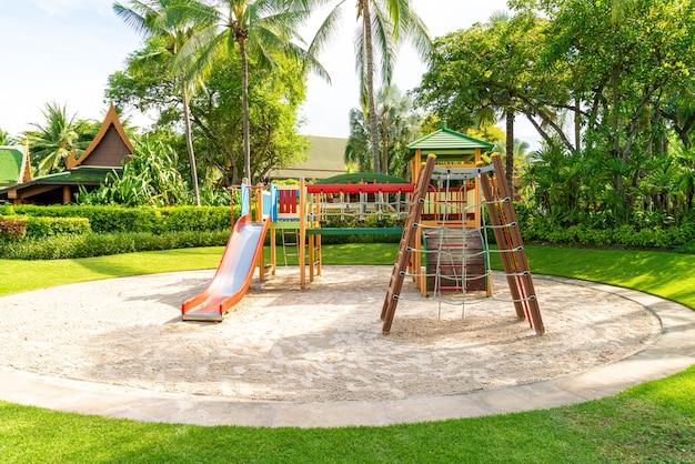 Plac zabaw dla dzieci, suwak umieszczony na piasku.